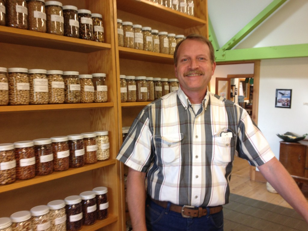 James Henderson of Hummingbird Wholesale smiles near wall of food he's helped grow.